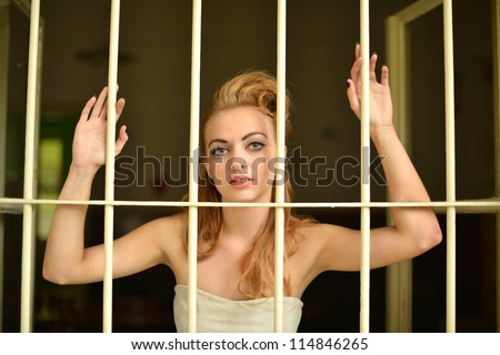 sexy young woman in a prison cell - stock photo