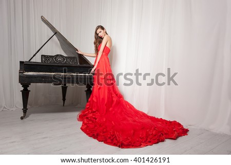 Sexy young woman in a red dress near a black grand piano, the background light - stock photo