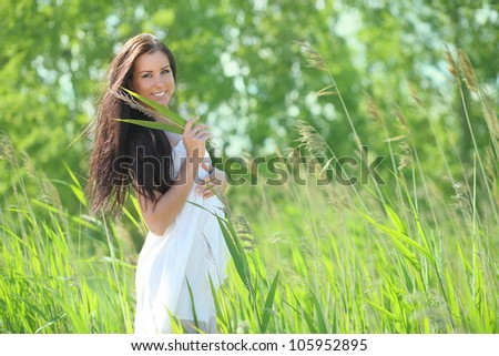 sexy young woman in a white dress in the grass, smiling - stock photo