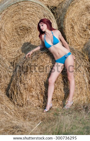 Sexy young woman in bikini against on haystack - stock photo