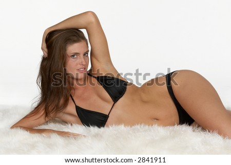 Sexy Young Woman in Black Bikini On Side on White Rug - stock photo