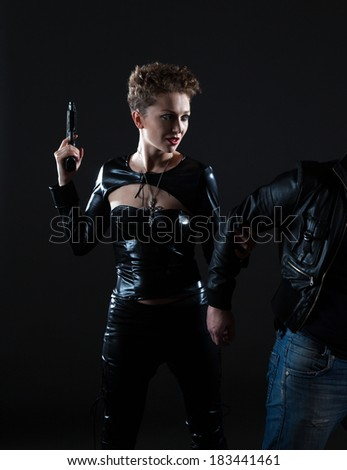 Sexy young woman in black leather suit holding a gun and grabs a man's hand  - stock photo
