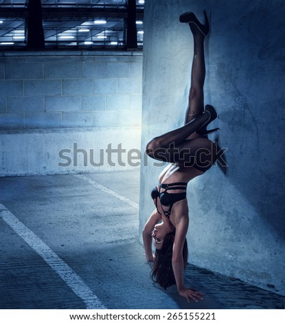 Sexy Young Woman in Black Lingerie with High Heels in Upside Down Pose While Leaning on the Wall Inside the Building. - stock photo