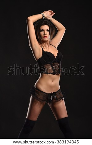 Sexy young woman in black seductive lingerie. photo in dark studio.