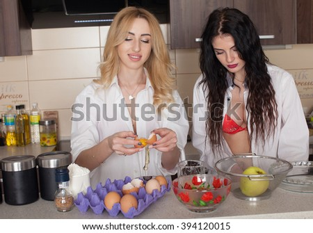 Sexy young woman in lingerie in her kitchen.  Fashion studio shot. Hot brunette and blond lady cooking some food with oven. - stock photo