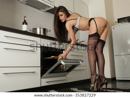 Sexy young woman in lingerie in her kitchen. Great ass. Fashion studio shot. Hot brunette lady cooking some food with oven.