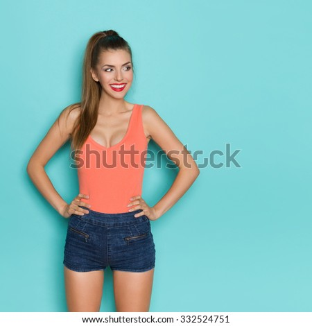 Sexy young woman in orange shirt and jeans shorts standing with hands on hip, smiling and looking away. Three quarter length studio shot on teal background. - stock photo
