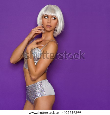 Sexy young woman in platinum wig and silver bikini looking away at copy space. Three quarter length studio shot on purple background. - stock photo