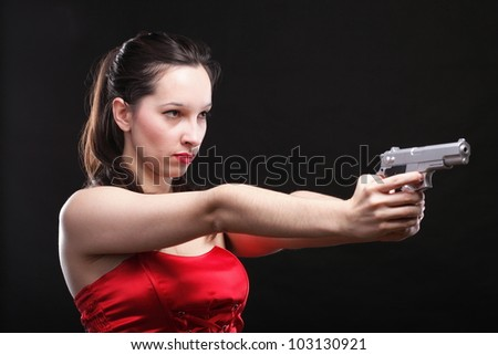 Sexy young woman in red with a gun on black background - stock photo