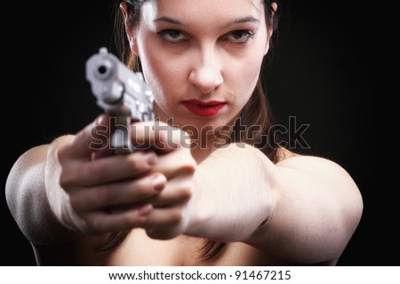 Sexy young woman in red with a gun on black background