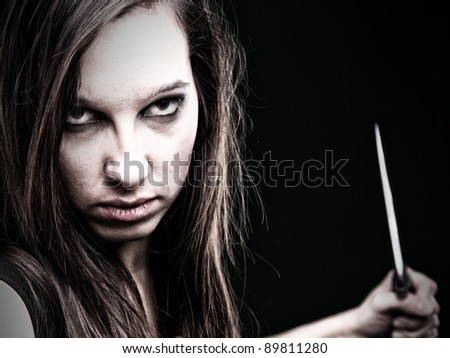 Sexy young woman in red with a knife on green background - stock photo