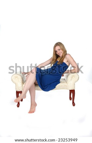 sexy young woman in short blue dress reclining on bench - stock photo