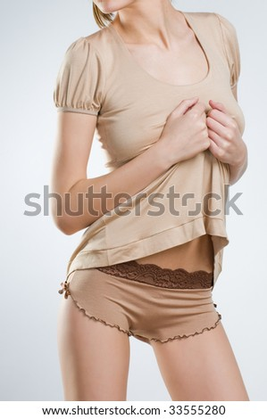 Sexy young woman in stylish beige lingerie, studio shot - stock photo