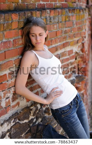 Sexy young woman in white tank top and blue jeans leaning against an old and weathered red brick wall - looking down with boot behind her on wall - stock photo
