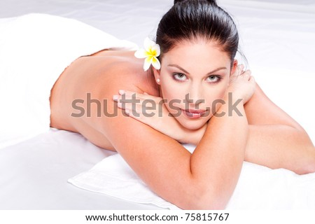 Sexy young woman lying on bed at spa center - stock photo