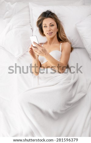 sexy young woman lying on the bed with phone. Above view - stock photo