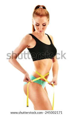 Sexy young woman measuring herself. Weight loss. - stock photo