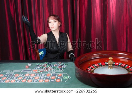 Sexy young woman playing in casino - stock photo