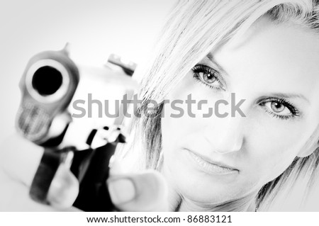 Sexy young woman pointing a gun Focus is on Woman - stock photo