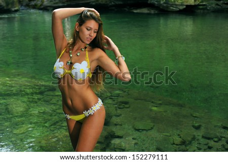 Sexy young woman posing in designer bikini at exotic location of mountain river with green water, rocks and forest in background - stock photo