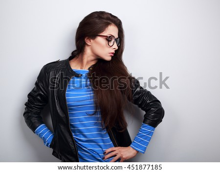 Sexy young woman posing in fashion black leather jacket and glasses on blue background with empty space