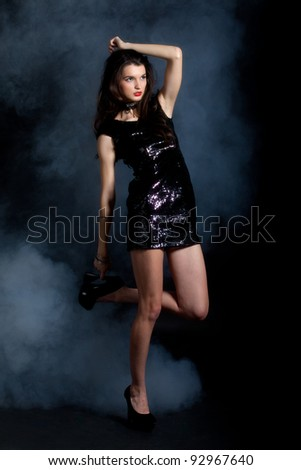 Sexy young woman posing in sequin dress, covered in fog, looking away. Studio image, on black background