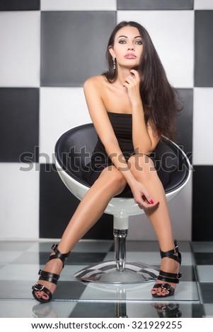 Sexy young woman posing on a chair in the studio