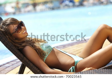 Sexy young woman relaxing on deck chair - stock photo