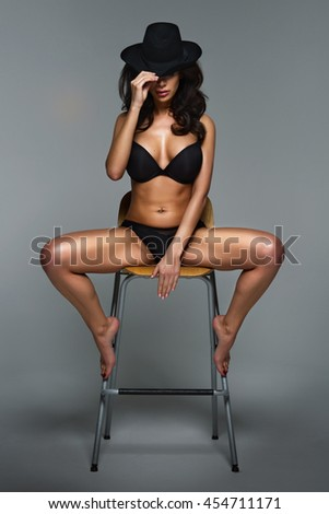 Sexy young woman sitting on a chair, wearing a hat.