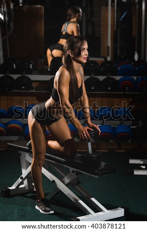 sexy young woman training with dumbbells workout in the gym