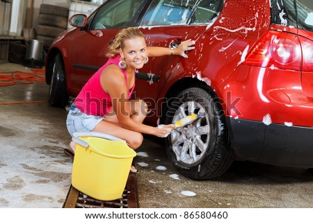 Sexy young woman washing the wheels of her car - stock photo