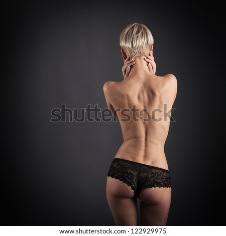Sexy young woman wearing lace pant from behind portrait against dark background. - stock photo