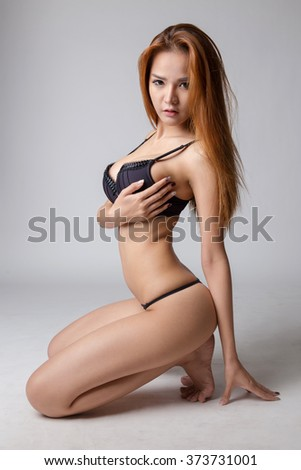 Sexy young woman wearing sexy black lingerie and thong sitting on the floor - stock photo