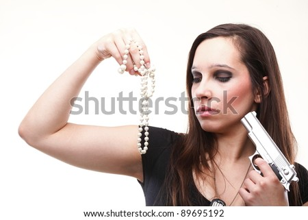 Sexy young woman with a gun and pearl isolated on white - stock photo