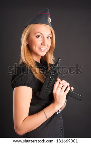 Sexy young woman with a gun at black. Focus on weapon - stock photo
