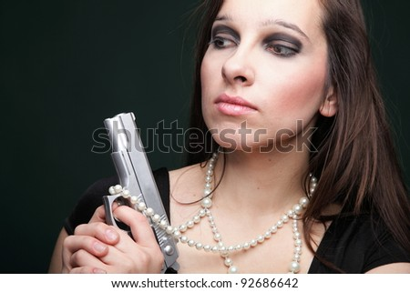 Sexy young woman with a gun, pearl on green background