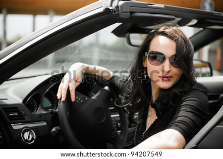 Sexy young woman with black sport cabriolet in summer - stock photo