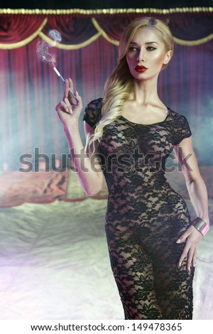 Sexy young woman with cigarette - stock photo