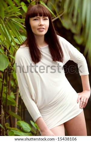 Sexy young woman with dark hair in tropical garden