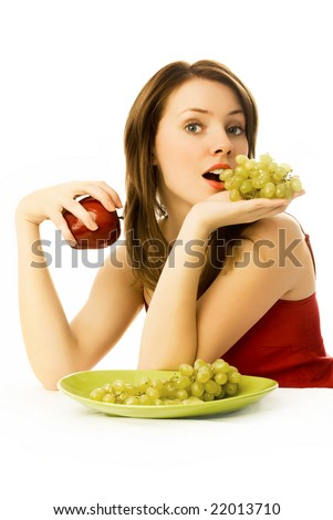 sexy young woman with grapes and an apple sitting by the table - stock photo