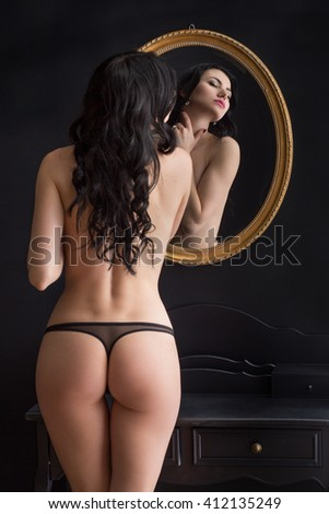 Sexy young Woman with great butt stands in lingerie in front of a mirror and shows her body and has some dreams - stock photo