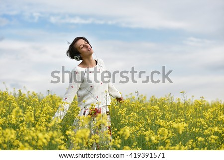 Sexy young woman with headphones dancing on music in the outdoors - stock photo