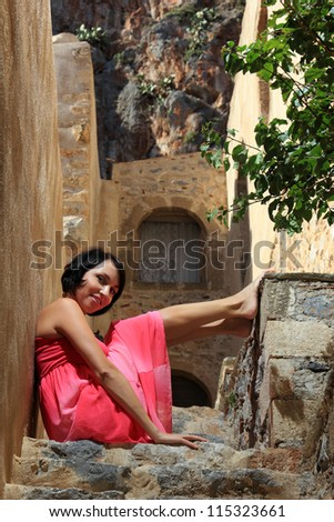 sexy young woman with pink dress on a beautiful traditional place in Greece - stock photo