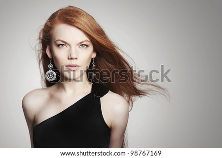 Sexy young woman with scatter red hair on grey background - stock photo