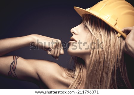 Sexy young woman with yellow safety helmet showing muscles against violet background - stock photo
