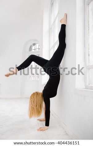 Sexy young yoga female doing handstand in white room against window in black sport suite - stock photo
