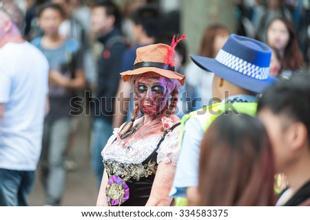 Sexy zombie girl at front of policeman at Sydney Zombie Walk in Sydney, AU, 31st October, 2015. Annual event where thousands of people get involved to raise awareness for Australia's Brain Foundation. - stock photo