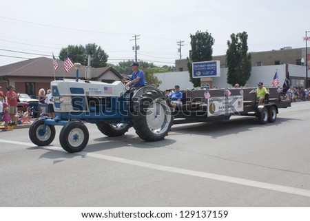 SEYMOUR, WI - AUGUST 4:  American Legion Tractor pulling Post 106 Seymour Veterans on a tractor at the Annual Hamburger Festival Parade on August 4, 2012 in Seymour, Wisconsin.