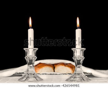 Shabbat candles in glass candlesticks with blurred covered challah background. Isolated on black. Copy space.  - stock photo
