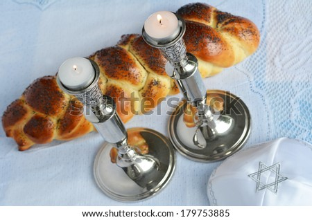 Shabbat eve table with uncovered challah bread, lit Sabbath candles and kippah. - stock photo